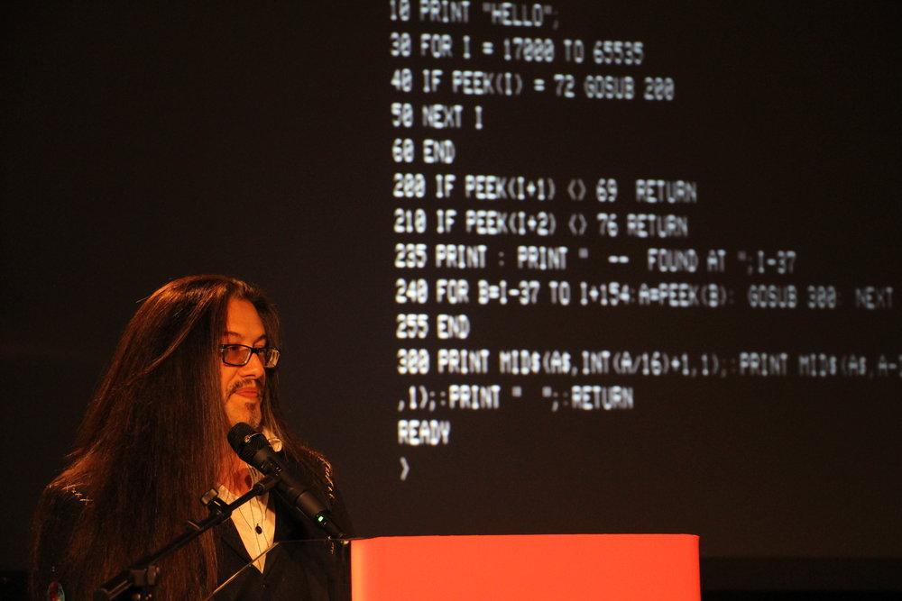 John Romero con del codice a caso sullo sfondo.jpg