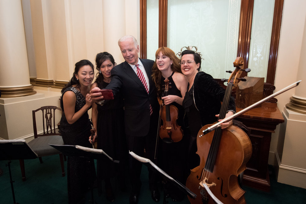 Former Vice President Joe Biden poses for a selfie with the string quartet