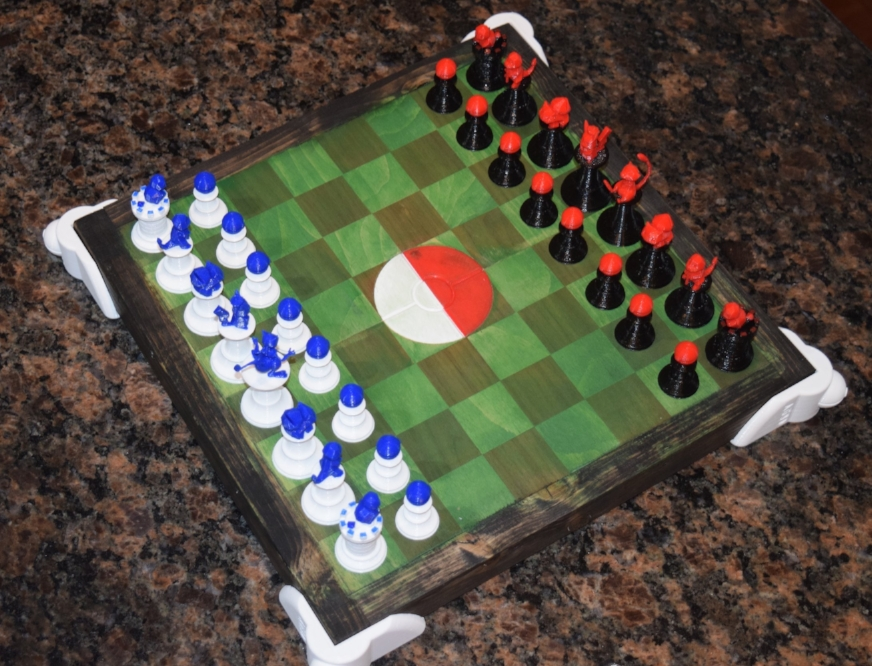 A birds-eye view of the Pokemon Stadium Chess Set. You can see the multi-color 3D printed Chess pieces, the 3D printed Pokeball center insert, and the stadium pokeball risers on the corners. These pieces were made using Hatchbox3D PLA and 3D printed with the Prusa i3 MK2