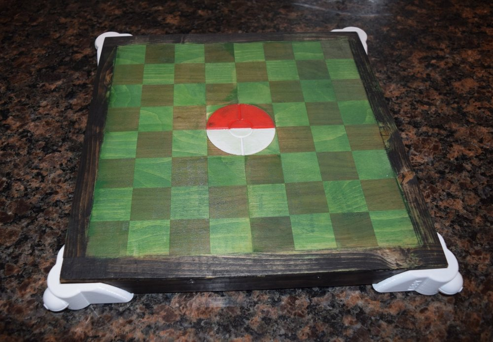 The Pokemon Stadium Chess board was the first time I had combined 3D printed parts with wooden products. I used a green stain to create the grass look of the stadium. The stained soft/hard wood created a weathered look that went very well with the final product. The 3D printed Pokeball insert and the Pokeball stadium risers really pop against the weathered look of the board itself. The accessories to the board were made using Hatchbox3D PLA and 3D printed with the Prusa i3 MK2