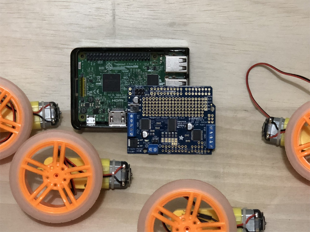 The Raspberry Pi (center-back), Pi Hat from Adafruit (center-front), wheels and TT motors. Batteries not included.