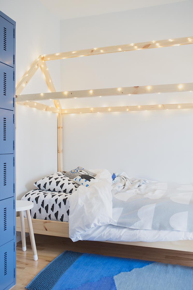 Péa les maisons. Un lit cabane illuminé dans une grande chambre partagée entre deux petits garçons et décorée dans les teintes de gris et de bleu