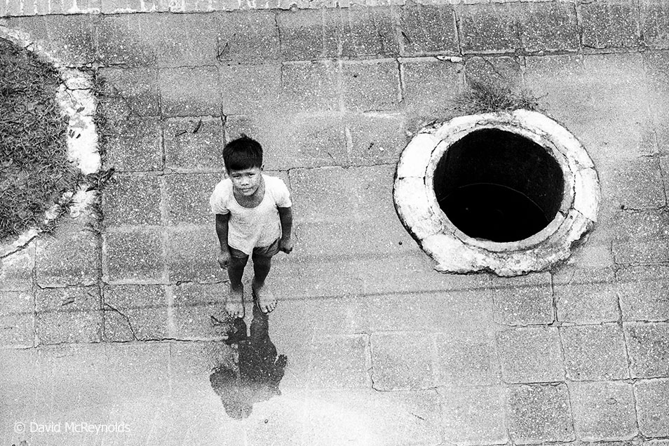 Child near sidewalk bomb shelter. Hanoi, 1971.