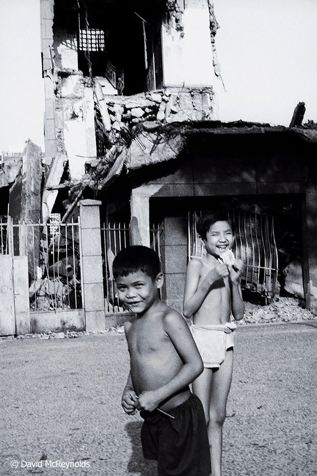 Boys in front of the destroyed national bank building.