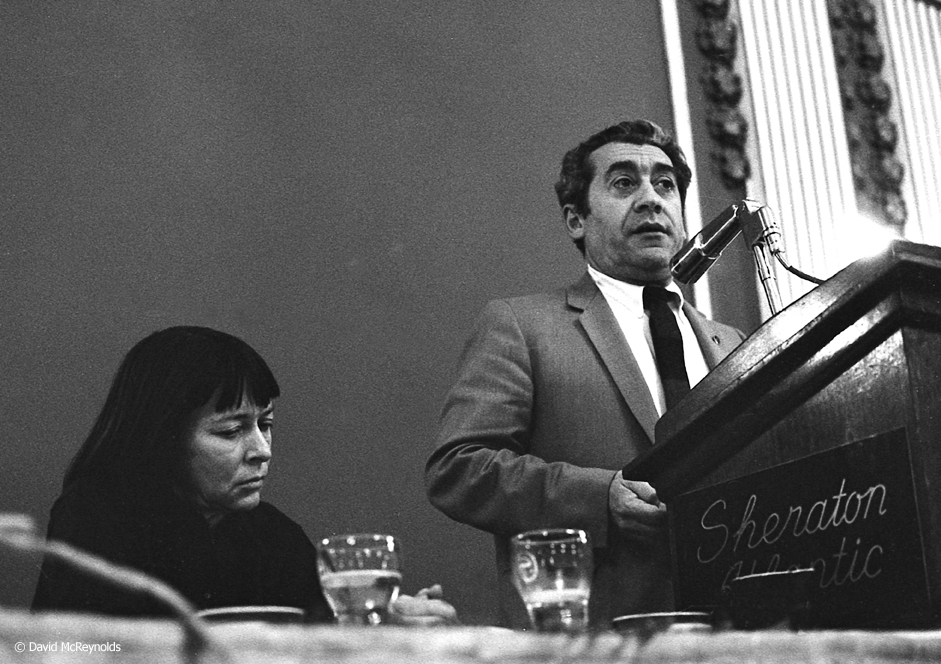 Ralph DiGia speaking at the 1967 WRL Peace Award Dinner where Barbara Deming, seated, was honored.