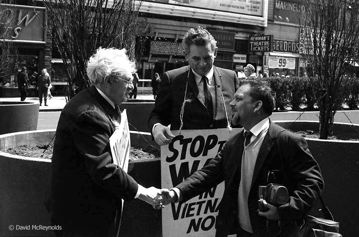 War Resisters' International (WRI) Secretary Devi Prasad (right) meets Otto Nathan at the weekly Times Square vigil to end the war in Vietnam. War Resisters League Chairperson Eddie Gottlieb is in the center. The vigil began in October 1964 and was co-sponsored by most New York peace organizations. April 29, 1967.