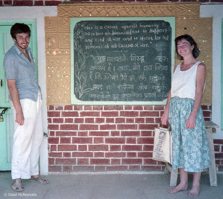 War Resisters' International staff members Howard Clark and Veronica Kelly. The board shows the WRI founding declaration in English and Hindi.