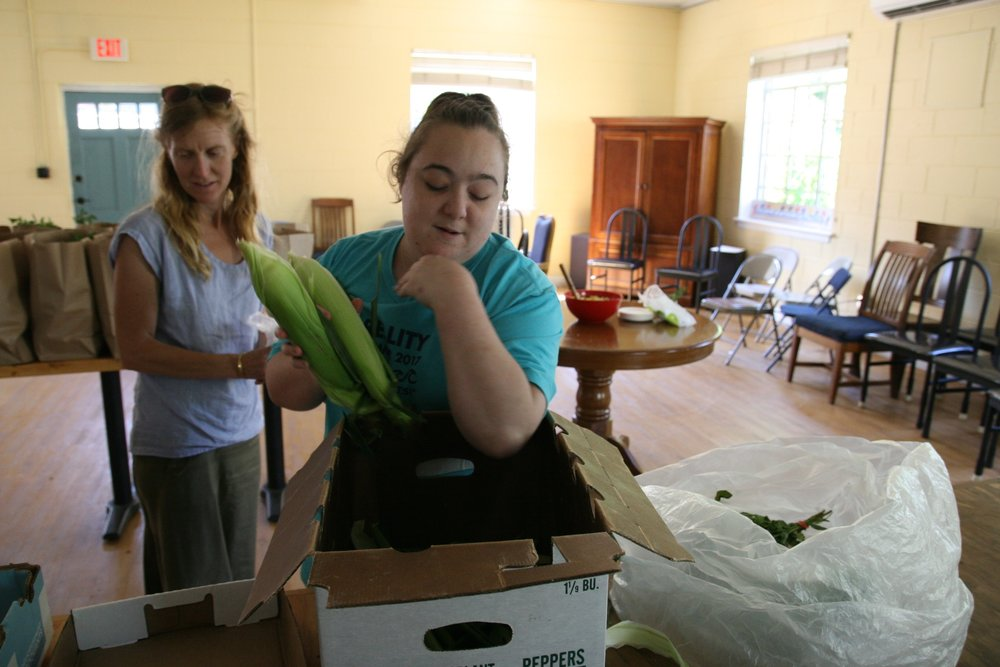 Kaitlan helps package corn into the shares.