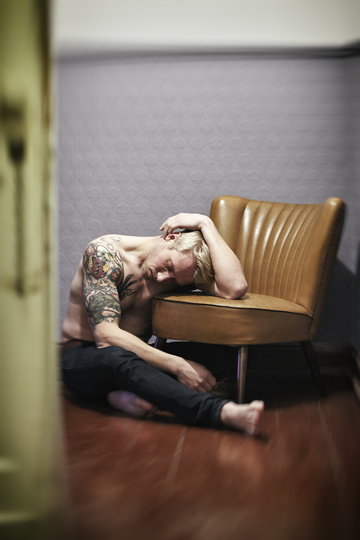Portrait-Mann-sitzt-auf-Boden-mit-Kopf-auf-Stuhl