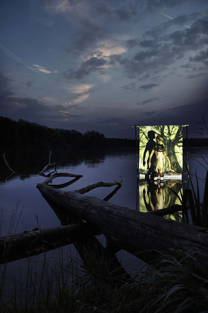 Projektion-Frau-steht-vor-angestrahlter-Leinwand-in-See