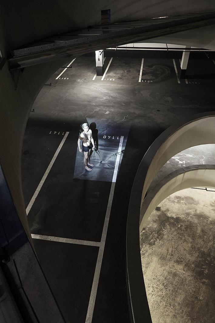 Projektion-Mann-steht-in-Parkhaus