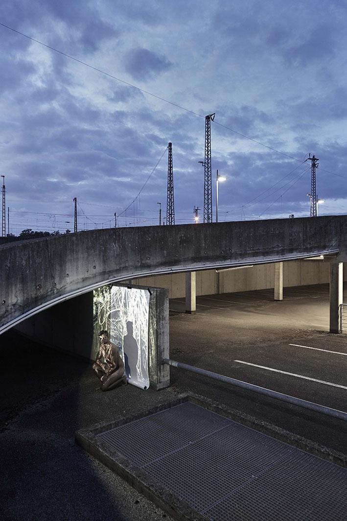 Projektion-Mann-kniet-vor-angestrahlter-Leinwand-auf-Parkplatz