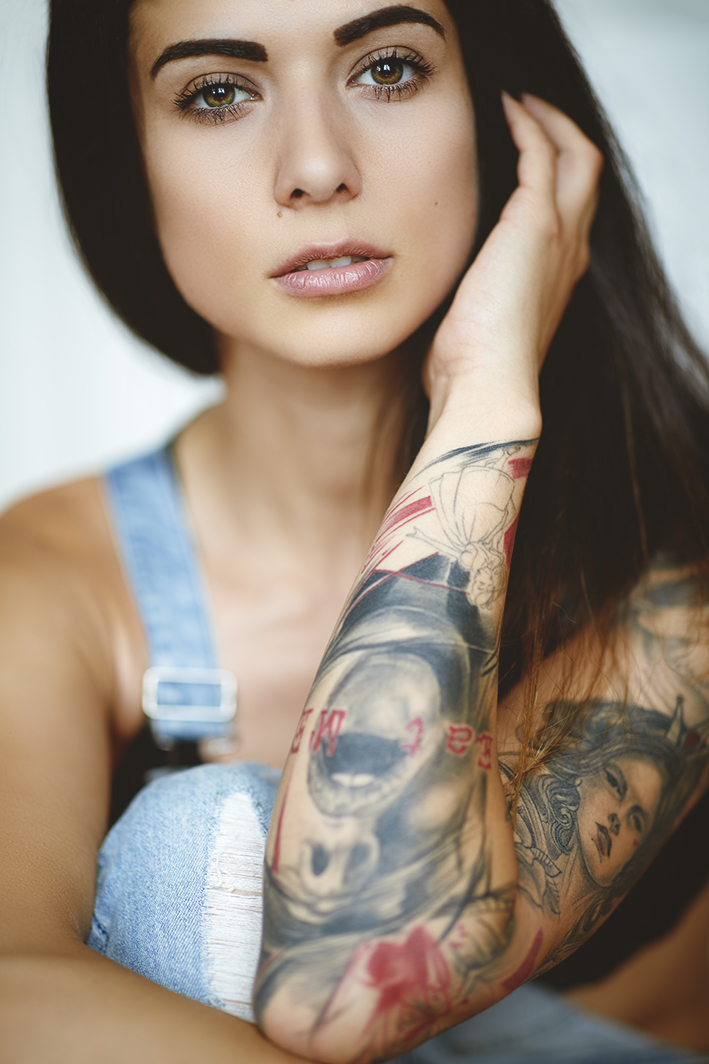 schwarzhaarige-Frau-mit-tätowiertem-Arm