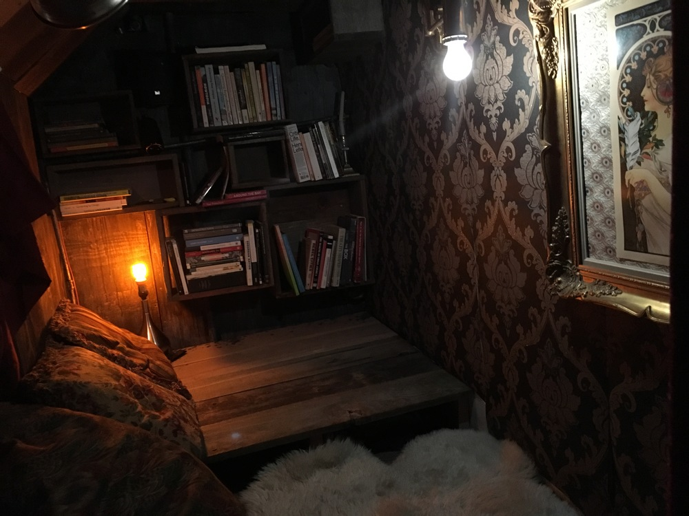 after  - recycled redwood fenceboards make up the floor and shelves, with vinyl damask wallpaper, Goodwill-sourced throw pillows, a shag rug, an old picture frame with an Art Nouveau poster, and dim lighting.