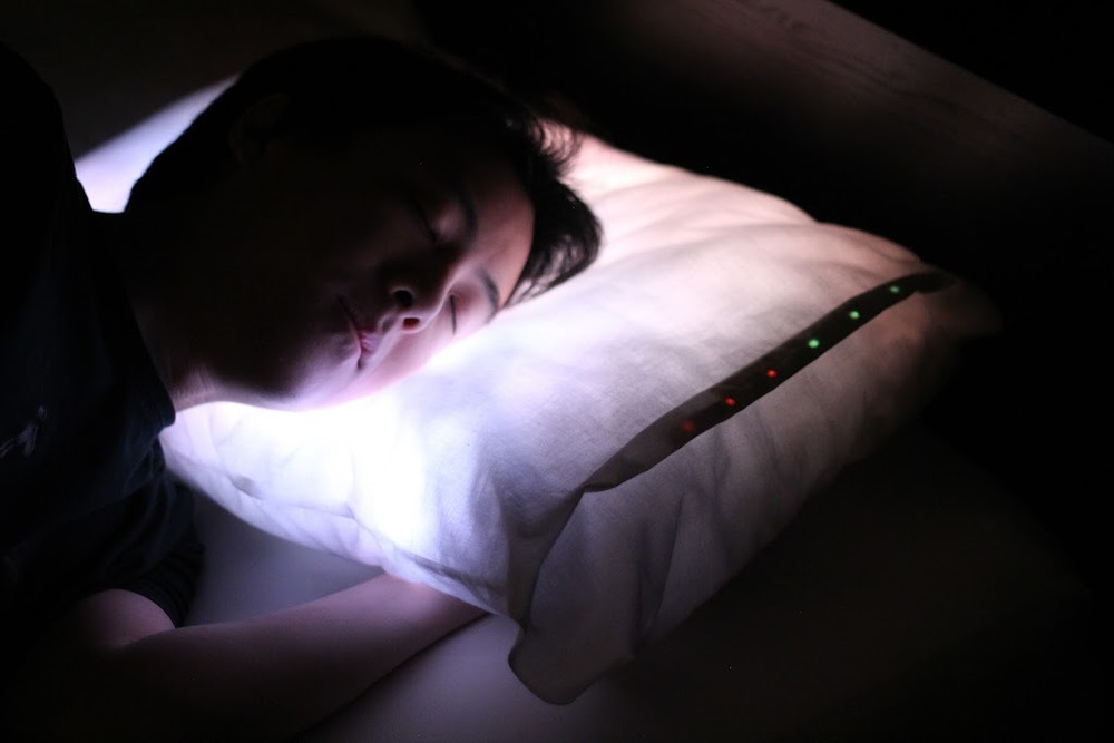The user trying the pillow in a dim room.