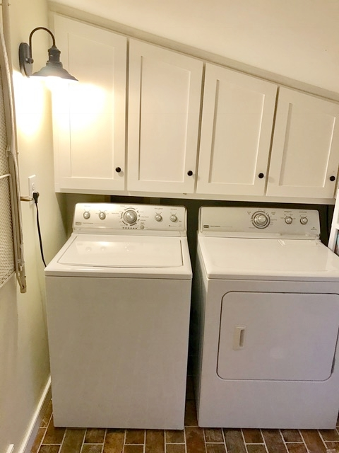 Built-in shelving and doors above washer and dryer