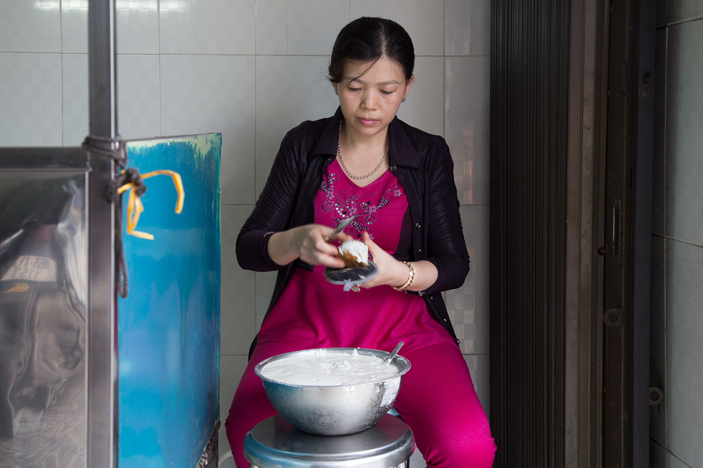 Madam Xung coating the banh cong in rice flour batter before it is refried.