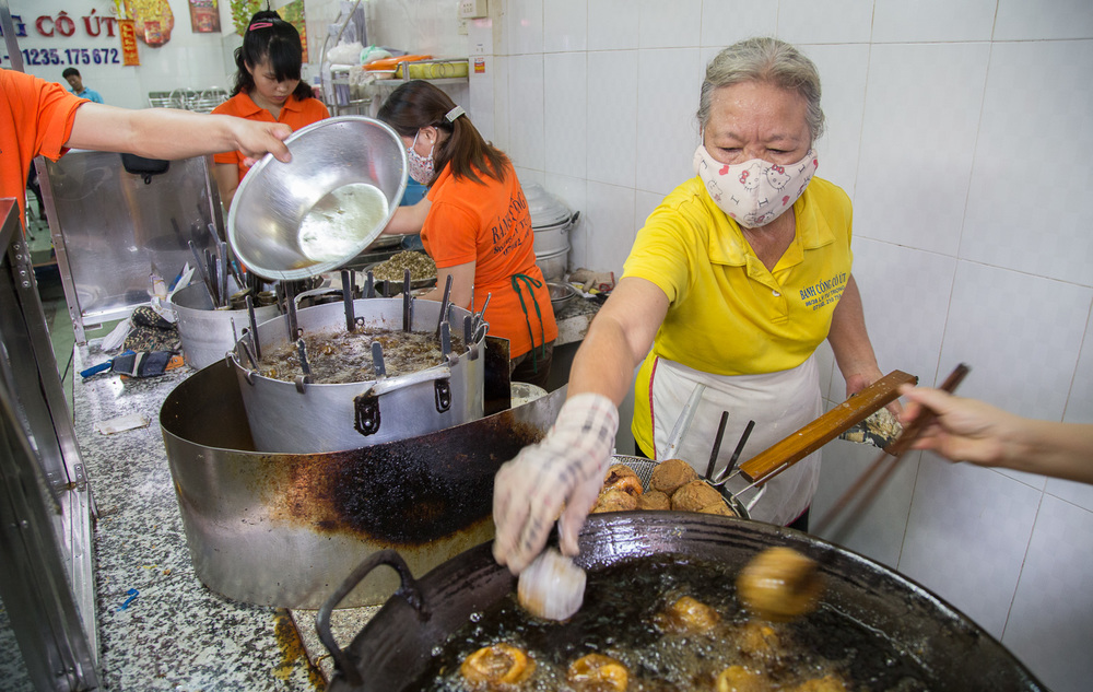 Incredibly hot work over the deep fryer at Banh Cong Co Ut as part of the busy production line.