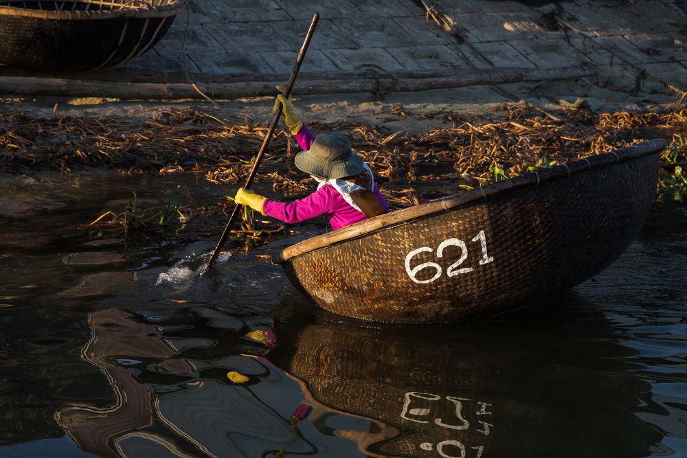 A local fisherwoman paddles her Thung Chai by gently waving the paddle back and forth through the water in an arcing motion.
