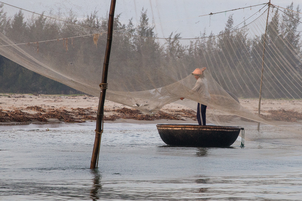"The fisherman guides the last fish of the catch across the net and into his ""Thung chai"" or bamboo boat."
