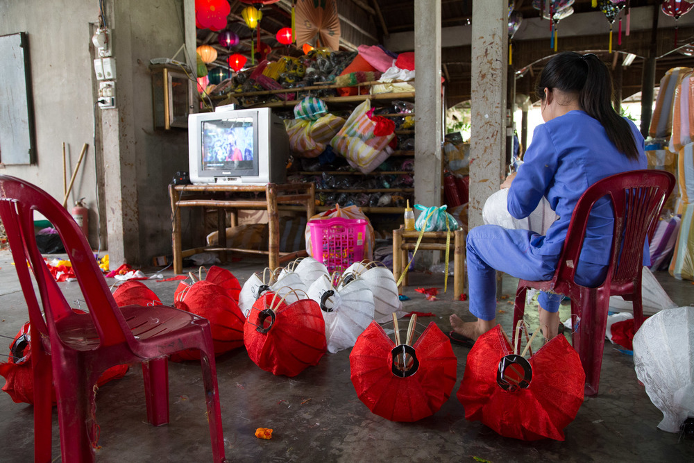 Vietnamese soap operas provide some relief from the repetition of lantern construction at Ha Linh lantern factory, Hoi An.