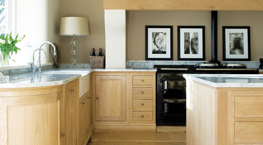 Neptune Henley Range – Light marble work surfaces on solid oak kitchen units with black Aga cooker