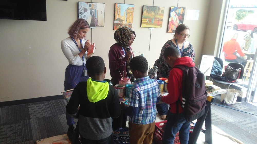 Teen Tech Squad members including Zubeda, center, along with community engagement librarian Sara Zettervall, right, help younger students with the afternoon's STEM-based project, sign painting with Springboard for the Arts.