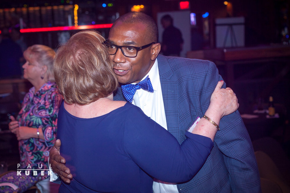 Kay Wilson hugs Terry Loftis, both board members of The Dallas Way
