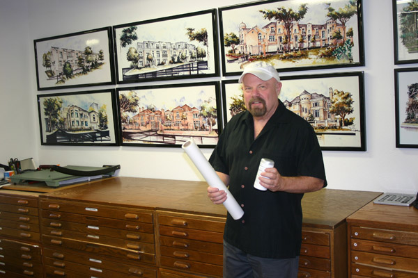 Mark Shekter standing in front of watercolors of various architectural projects he created.                                                           ( Image courtesy of  Dallas Voice )