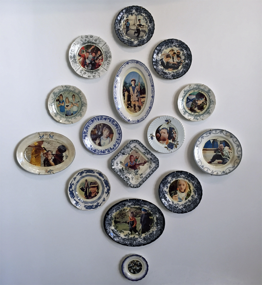 Pixelated to protect the innocent: Kids will be Kids , 2013, Wall installation of vintage dinnerware with appropriated images of children with guns from the internet, 60 x 46 x 2.5 inches
