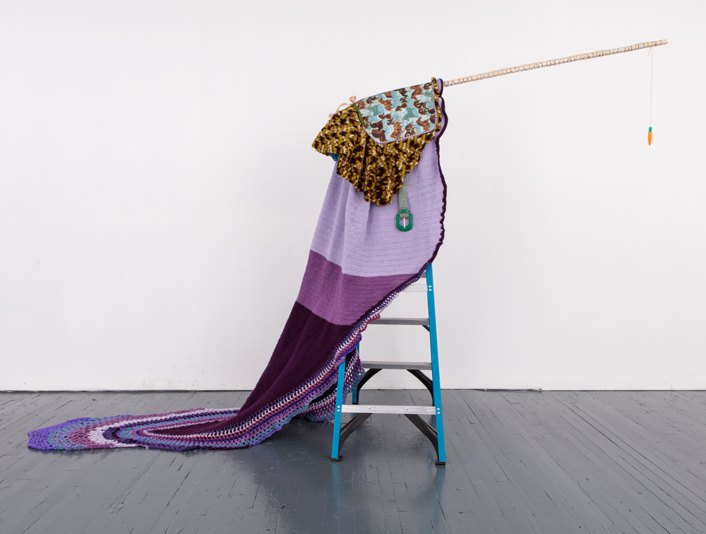 "Just Out of Reach,  2014, fabric, felt, yarn, ribbon, acrylic. paper clips, plastic, carrot, PVC pipe, plaster, shoe, belt, 6ft, ladder, 83""x 140""x 41"""