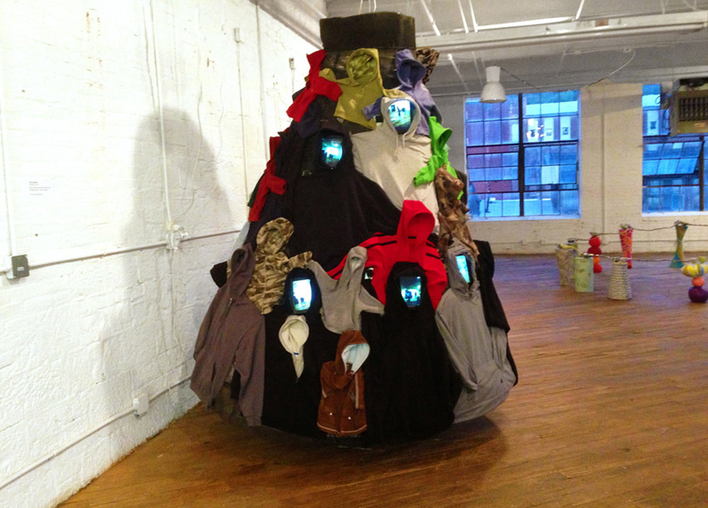 """SmartSkirt (hoodie skirt)"". Video Installation Social Sculpture, 2015. Mixed-media, 24 micro-video cameras and monitors. 84"" Diameter X 93"" H."