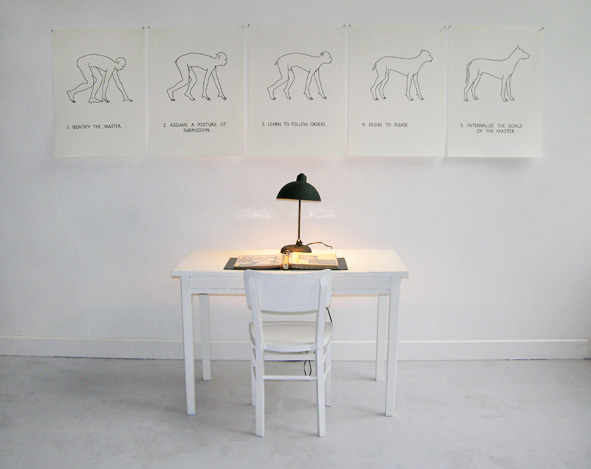 "How Do Men Turn Into Dogs? , 1975  Installation with the form of a ""learning center"" consisting of: Table, chair, lamp, notebook with documents comparing dog training with job training, with five posters: Identify the master — assume a posture of submission — learn to follow orders — desire to please — internalize the goals of the master."