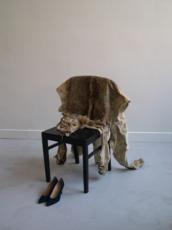 Shaper Shifter,  2005  Chair, lion skin, high fashion shoes  A text is engraved on one of the soles of the shoes: Quand l'univers s'abîmera dans la destruction, Loki triomphera avec un éclat de rire diabolique.