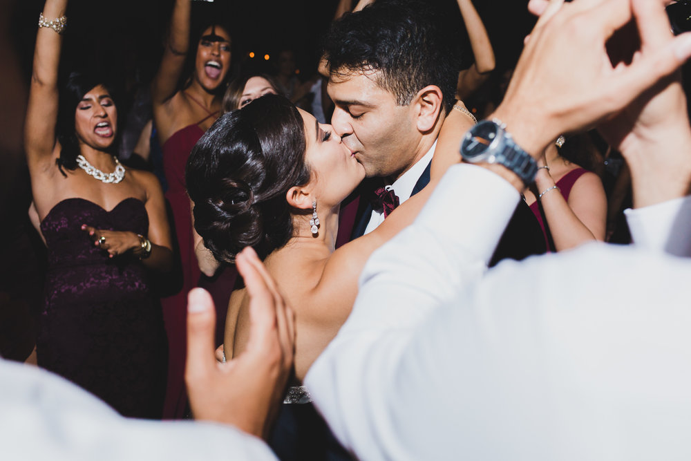 bride and groom kissing during wedding reception at the swan house museum ball room