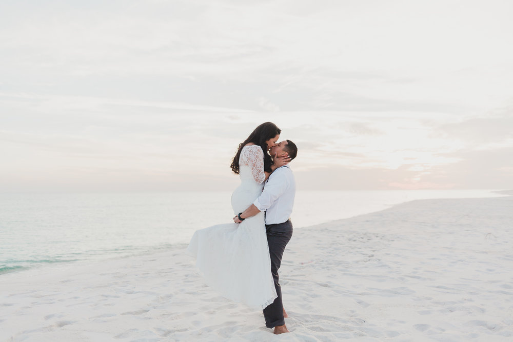 bride carrying groom pose on pensacola beach