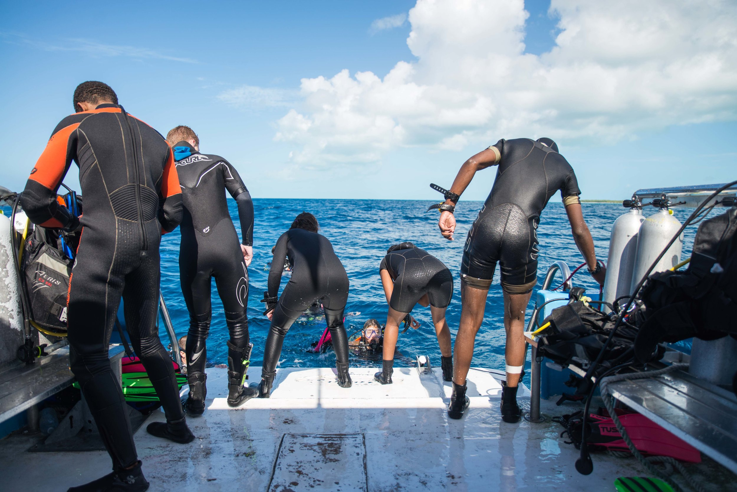Students helping each other back on the Cobia before another dive