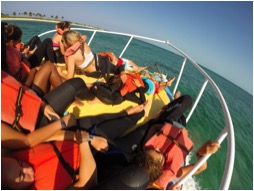 Students relaxing on the Cobia on the way out to The Barge.