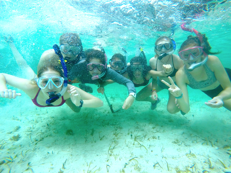 A group of students piling in for a group photo while having fun at the sandbar!