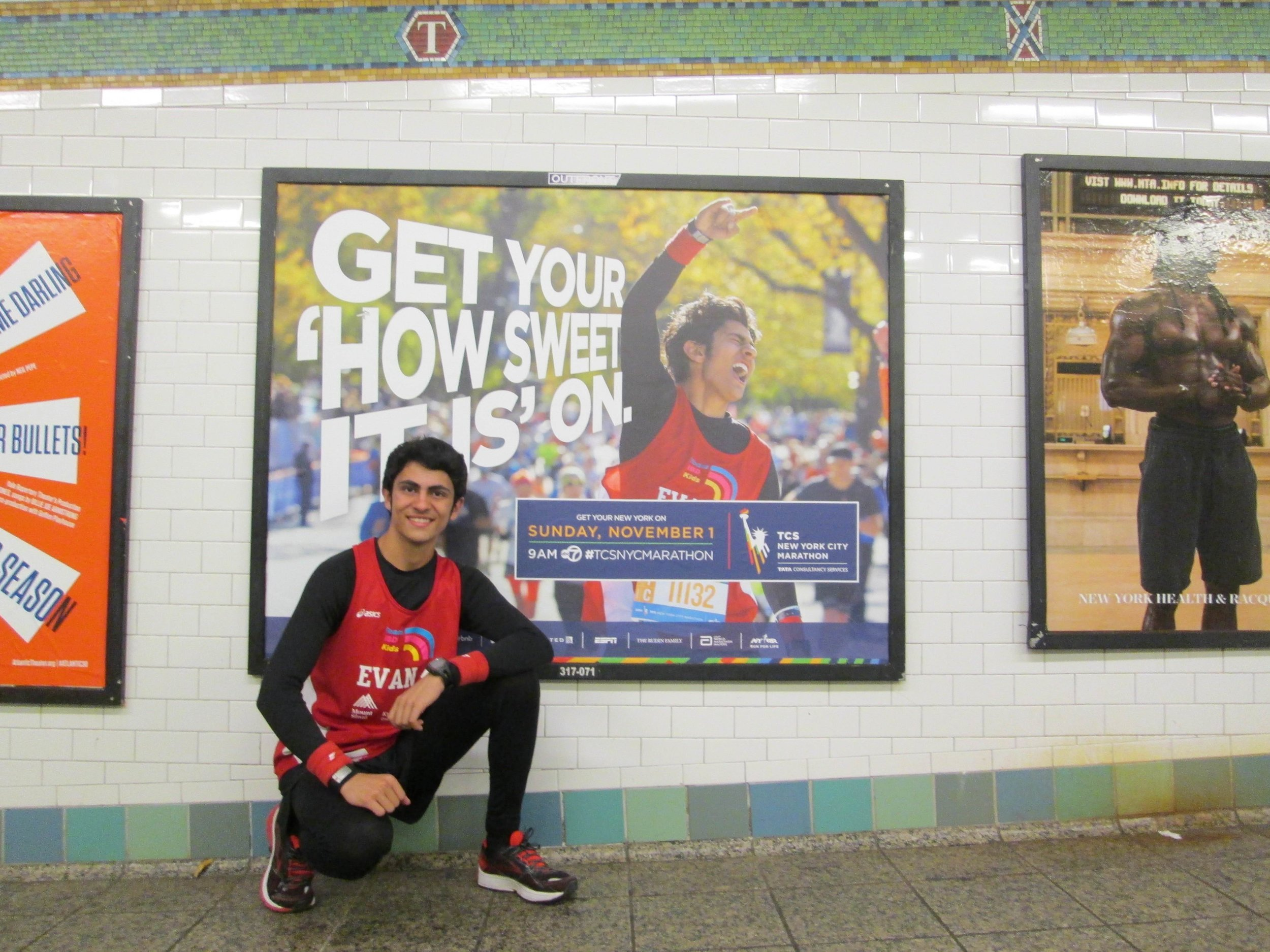 Evan in front of a New York Road Runners subway advertisement for the NYC Marathon