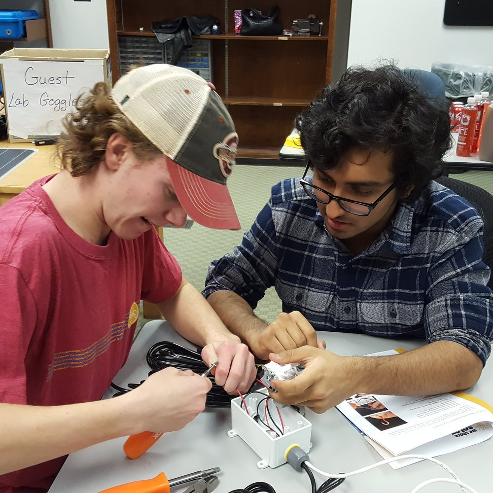 Island School alumni Nick Giordano (Spring 2016) and Azam Janmohamed (Spring 2016) hard at work  assembling the components of a solar suitcase destined for PPS.