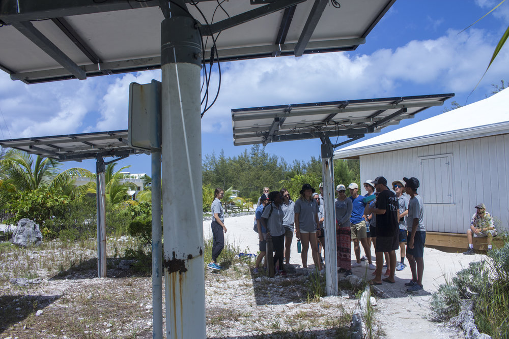 In this image, students are seen learning about the benefits of pole mounted solar rays.