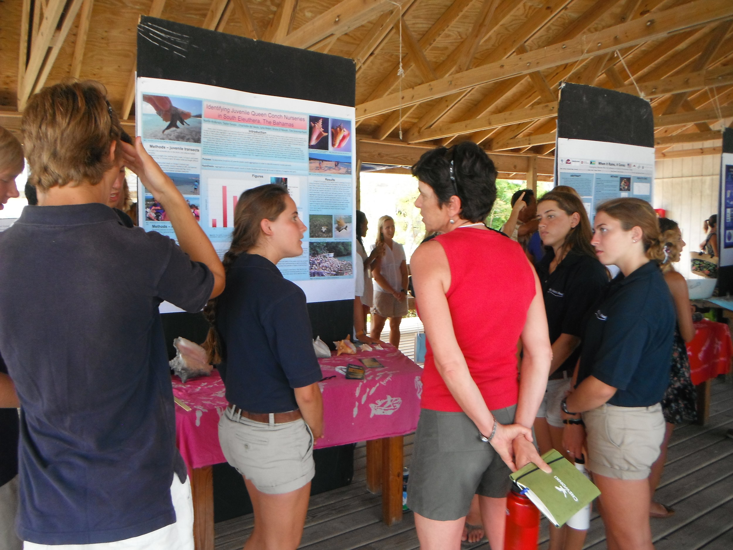 Students engaging a visitor, answering questions on their research.