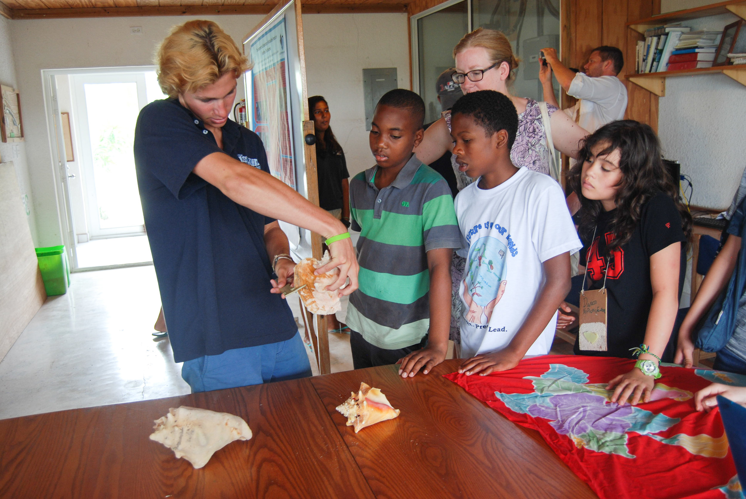 Spring 15 Island School student shows a tour group how to measure a queen conch. Photo credit: Cam Powell