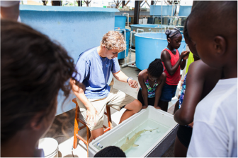 an Bouyoucos, M.Sc candidate at the University of Illinois, prepares to show the students a juvenile lemon shark.
