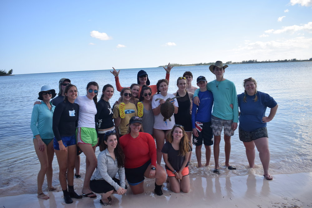 The volunteers from Dover-Sherbourne High School gather for a group photo on the shoreline of a creek where they spent the day spot-seining to catch turtles.