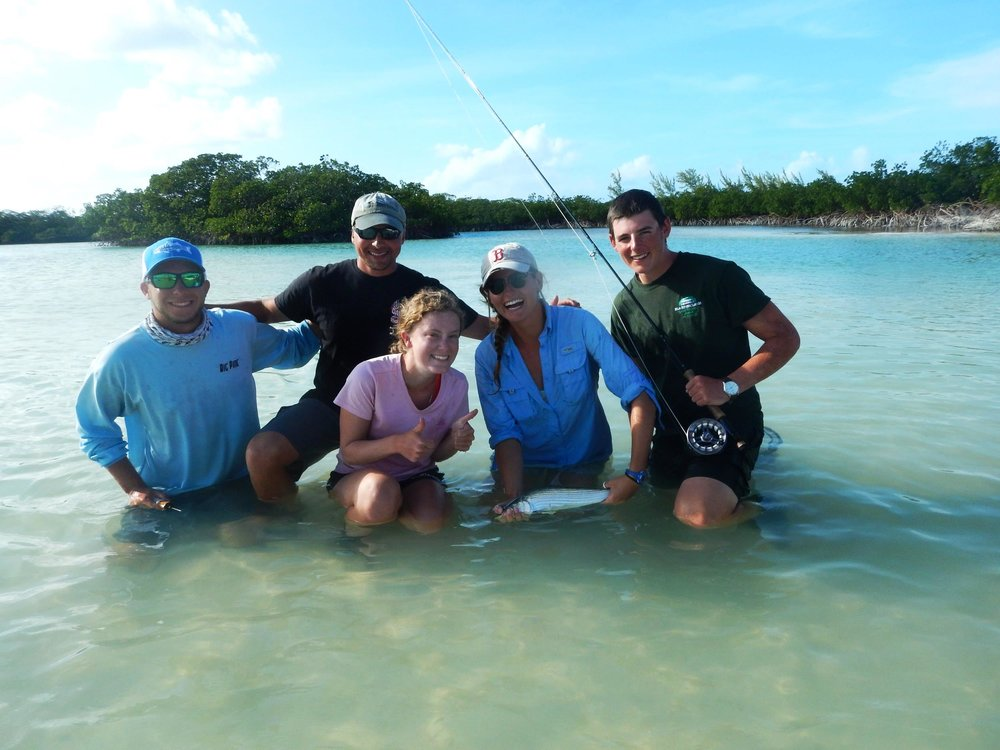 The team happily poses with a bonefish after another successful field day.