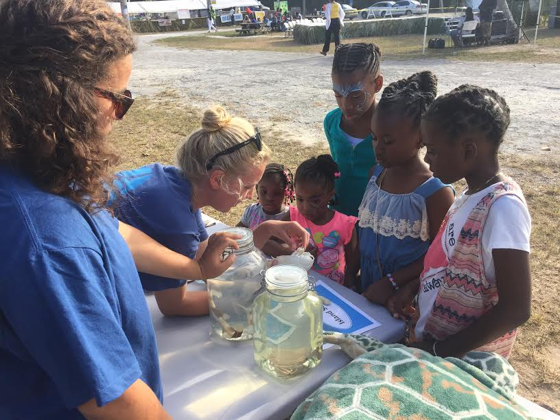 CEI interns and graduate students show off some deep sea specimens to local children.
