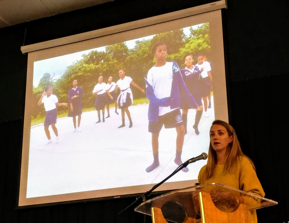 Candice Brittain presenting the parrotfish research, and showing an image of Deep Creek Middle School students preparing a skit to perform in their communities conveying the importance of parrotfish to the marine ecosystem.