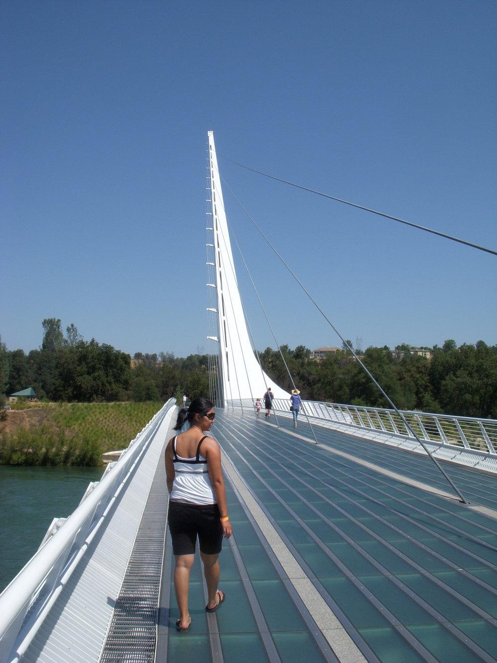 Mai walking across bridge